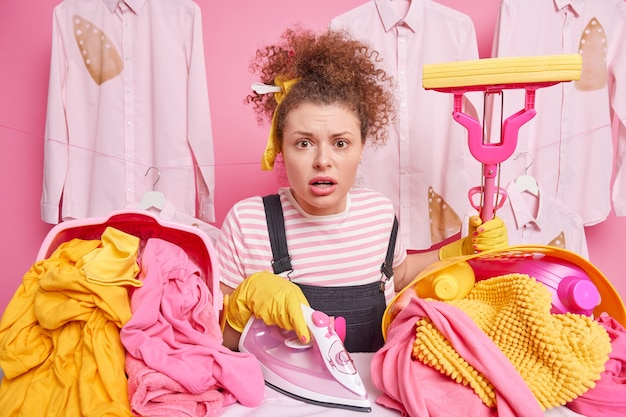 Routine work and household concept. worried impressed housewife with curly hair holds mop poses near ironing board with electric iron tidies up clothes brings pile of laundry busy doing housework