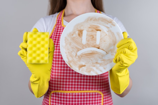 일상적인 작업 작업 일상 개념. 압도 과로 좌절 스트레스 우울 미친 아내의 자른 가까이 접시 고립 된 회색 벽에서 흙을 씻어 준비