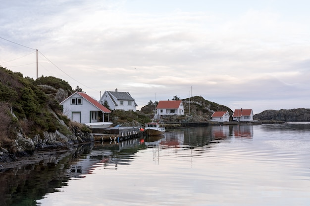 Rovaer в хаугесунде, норвегия - 11 января 2018 г .: архипелаг rovaer в хаугезунде, на норвежском западном побережье. пирс и рыбацкая лодка, дома у моря.