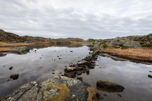 Пруд на тропе, на архипелаге rovaer, остров в хаугесунде, норвегия. камни делают путь через воду.