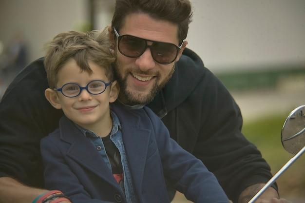 2020年2月19日、イタリア、ロビゴ:笑顔の父と息子がスクーターで旅行