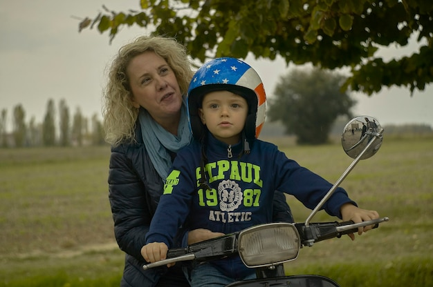 2020年2月19日、イタリア、ロビゴ:笑顔の母と息子がスクーターで旅行