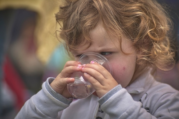 Rovigo, italy 21 july 2021: child drinks from the glass