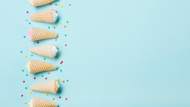 Row of aalaw in the waffle cone with sprinkles on blue background
