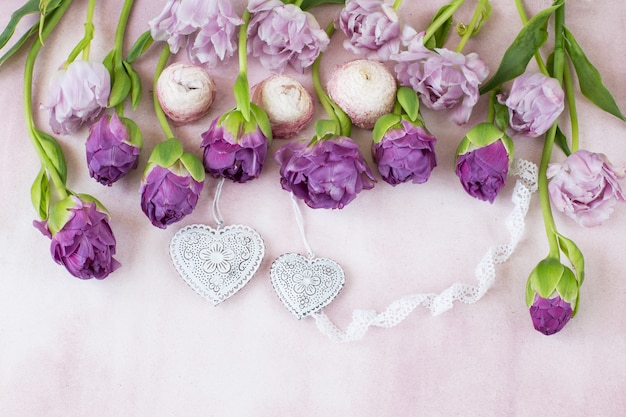 A row are purple tulips, a ribbon of lace and two hearts