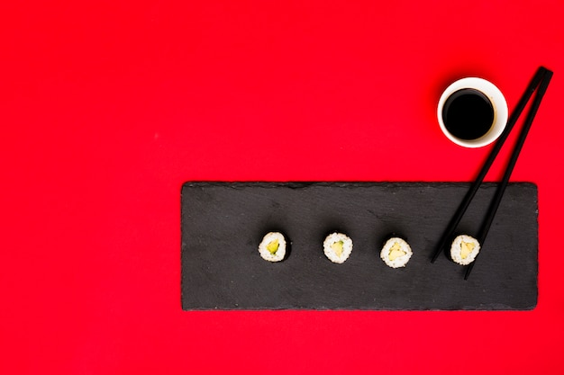 Row of asian rolls on slate plate with chopsticks and soya sauce over red backdrop