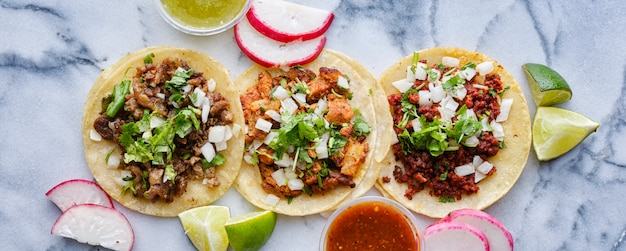 Row of assorted mexican street tacos with garnishes in wide banner composition