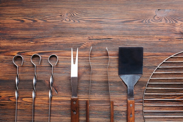 Row of barbecue utensils on wooden table