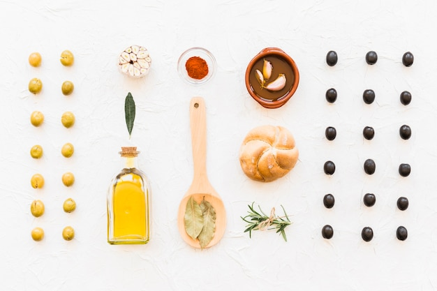 Row of black and green olives with oil bottle and ingredients on white background