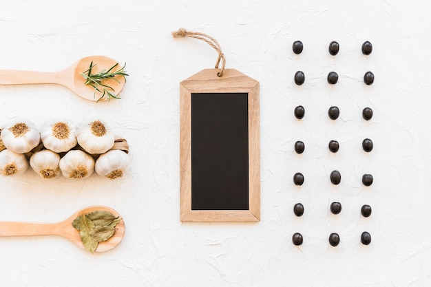 Row of black olives with empty black slate and bunch of garlic bulbs