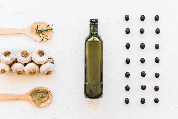 Row of black olives with oil bottle, garlic bulbs, and herbs on white textured backdrop