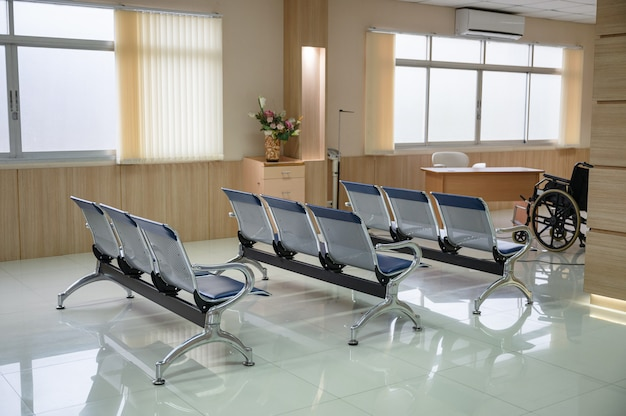 Row of blue empty chairs and wheelchair in waiting room at hospital