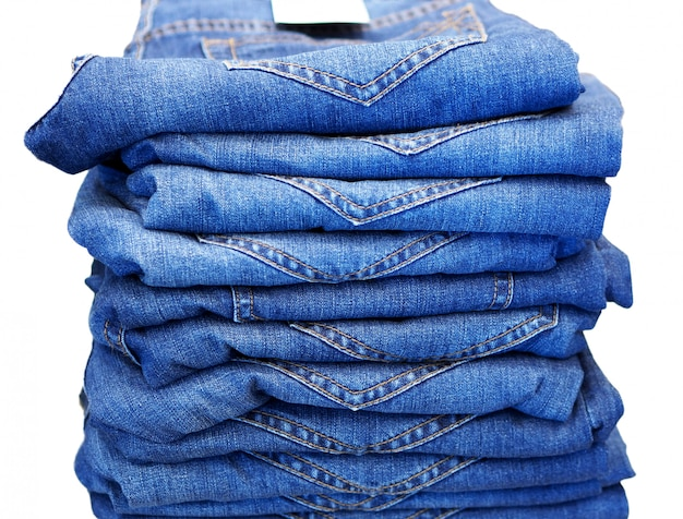 Row of blue jeans. white background close up.