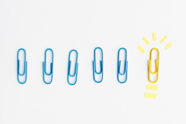 Row of blue paperclips arrange near yellow paper clip showing idea concept