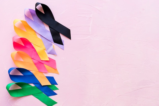 Row of bright colorful awareness ribbon on pink rough background