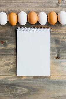 Row of brown and white eggs near blank notepad on wooden desk