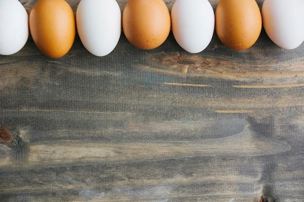 Row of brown and white eggs on wooden background