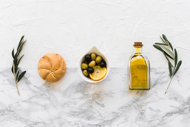 Row of bun, olives and oil bottle with two twigs on white marble