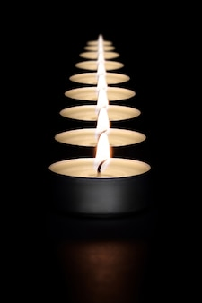 A row of burning candles on a dark background with a flare in the foreground. layout, mockup.