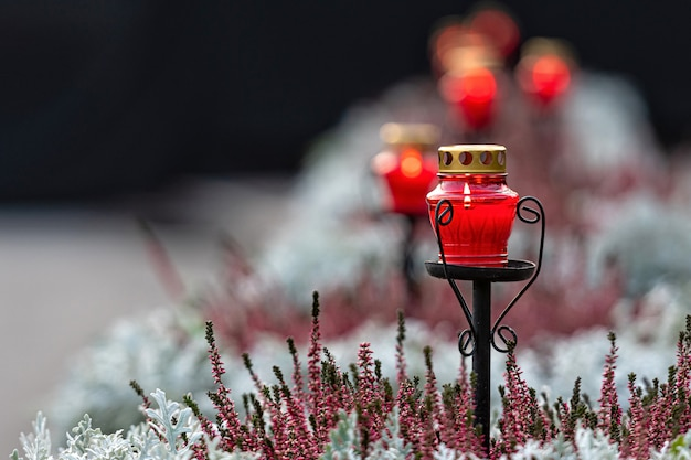 Row of burning candles in red glass holders on a defocused floral background at night