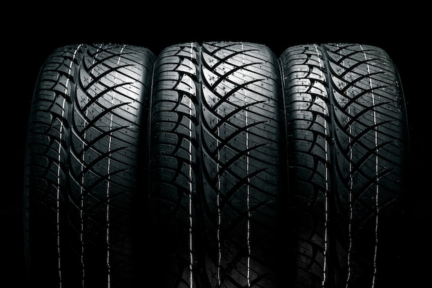 Row of car tires with a profile close-up on a black