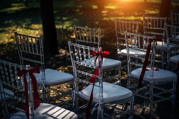 Row of chairs for outdoor wedding ceremony, close-up. chairs are prepared for the reception.