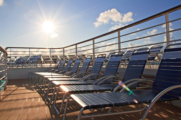 Row of chaise longues on deck of cruise ship. golden sun shining.