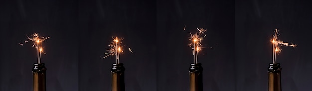 Row of champagne bottle with fire sparkler against black background