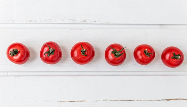 Row of cherry tomatoes on a white wooden table. vegetarianism and a healthy lifestyle. panorama format. top view. space for text.