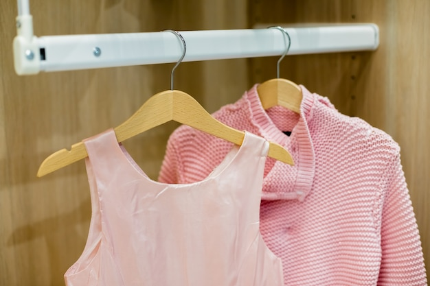 A row of children clothes hanging on hangers.