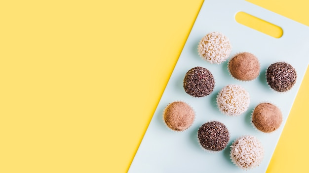 Row of chocolate truffles on white chopping board against yellow background