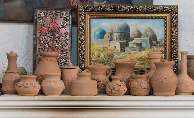 Рядные глиняные горшки на фоне картин. детские поделки