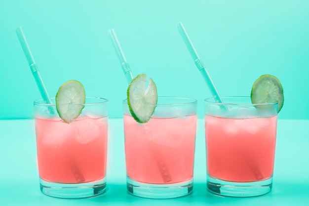 Row of cocktail glasses with ice cubes; drinking straw; lemon slices on mint background