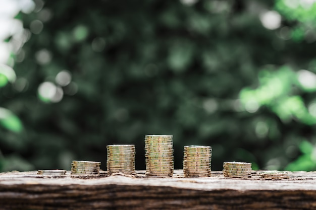 Row of coin money on wood table with green nature background, real estate market.