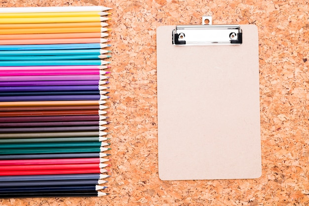 Row of color pencils and clipboard on cork background overhead