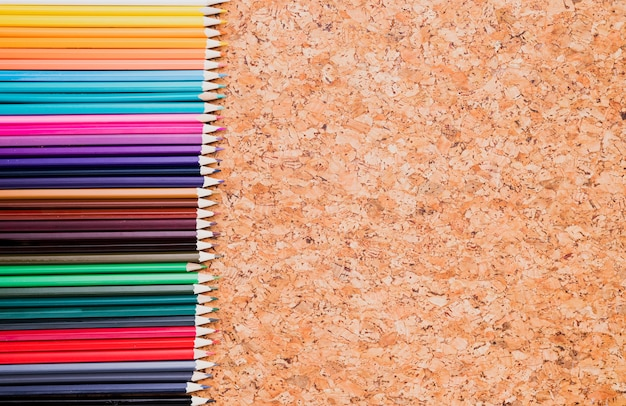 Row of color pencils on cork background top view