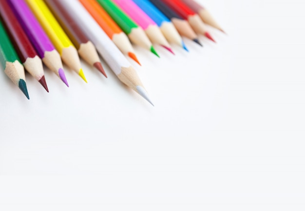 A row of colored sharp tip pencils on white background