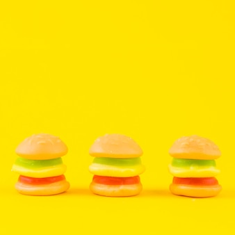Row of colorful burger candies on yellow background
