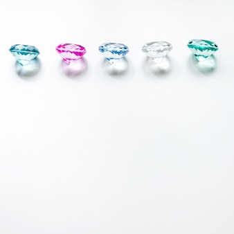 Row of colorful diamonds with shadow on white background