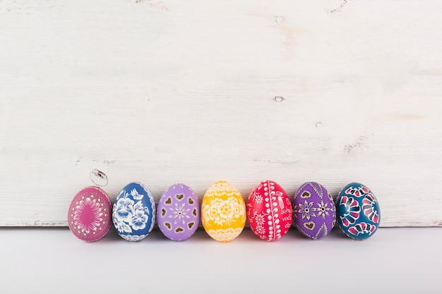 Row of colorful eggs on wood