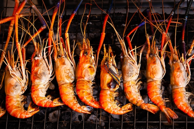 Row of colorful grilled praws on hot fire.