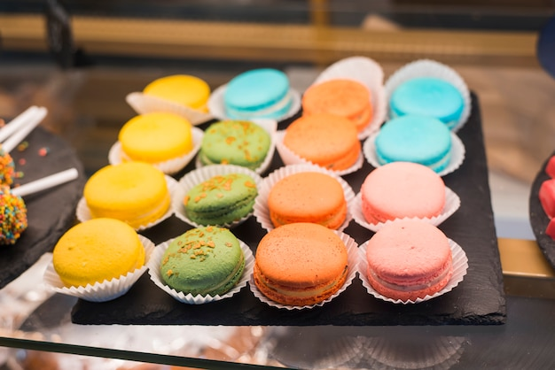 Row of colorful macaroons on the slate plate in the glass cabinet