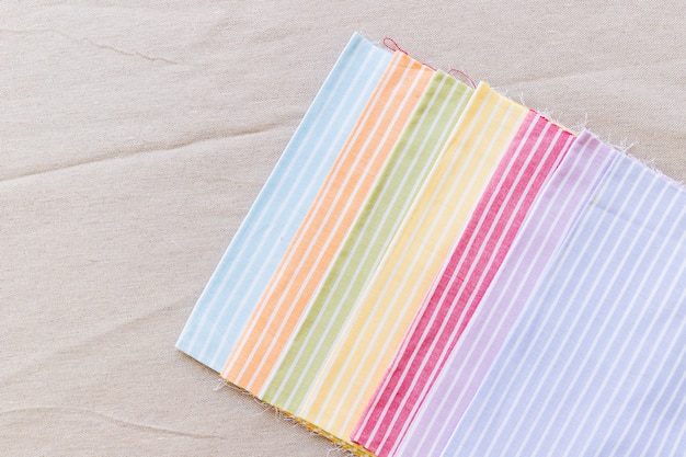 Row of colorful stripes pattern curtain samples on textile surface