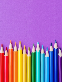 Row of colorful watercolor pencils on lilac background. school supplies