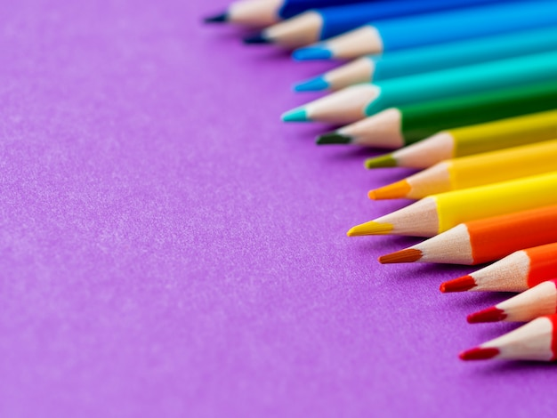 Row of colorful watercolor pencils on lilac.
