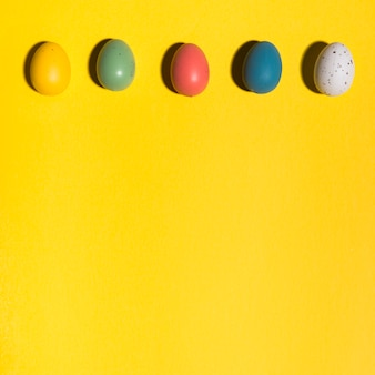 Row of colourful easter eggs on yellow table