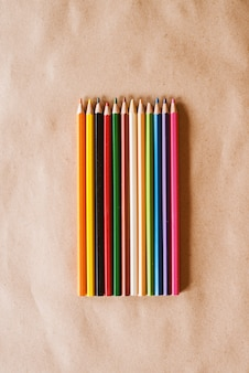 Row of colourful wooden crayons on the desk.