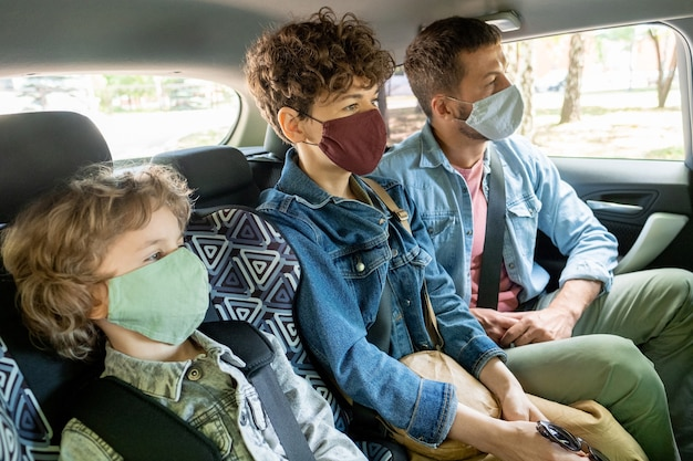 Row of contemporary young family of three in protective masks and denim jackets looking forwards while going by car on backseat