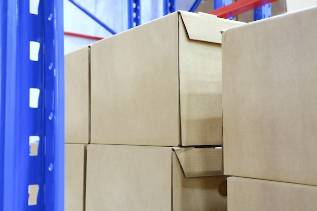 Row of cotton boxes kept in warehouse shelves ;