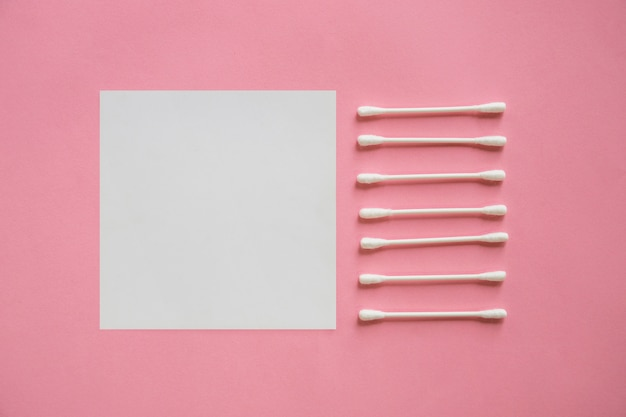 Row of cotton swabs near the blank adhesive note on pink background